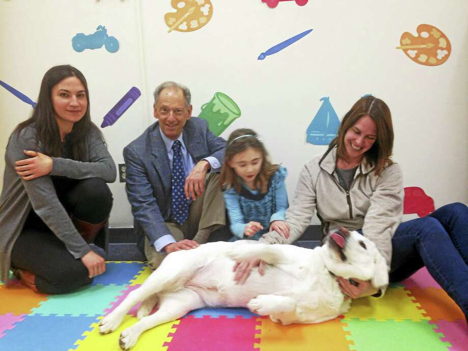 Relaxing with Pards, an English white Labrador, are, from left, Molly Crossman, Alan Kazdin, Chloe Nelson and Kim Crosby, Pards' companion. Photo: ED STANNARD — NEW HAVEN REGISTER