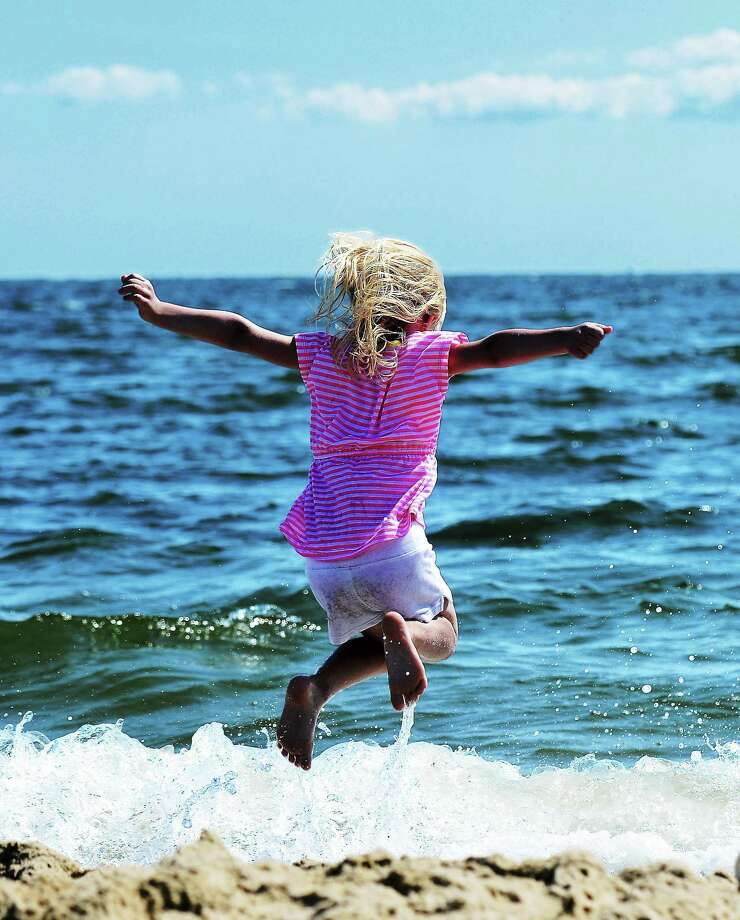 Olivia Howland, 5, enjoys the raging surf at the West Haven Beach across from Chick's Drive-In. Photo: PETER CASOLINO — NEW HAVEN REGISTER FILE PHOTO