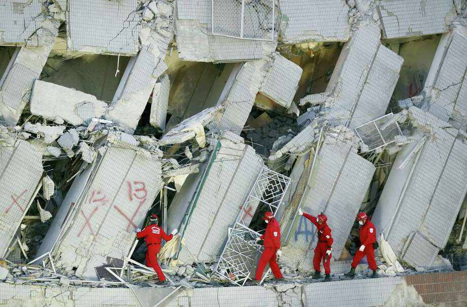 Emergency rescuers continue to search for missing in a collapsed building from an earthquake in Tainan, Taiwan on Feb. 7, 2016. Rescuers on Sunday found signs of live within the remains of the high-rise residential building that collapsed in a powerful, shallow earthquake in southern Taiwan that killed over a dozen people and injured hundreds. Photo: AP Photo/Wally Santana   / AP