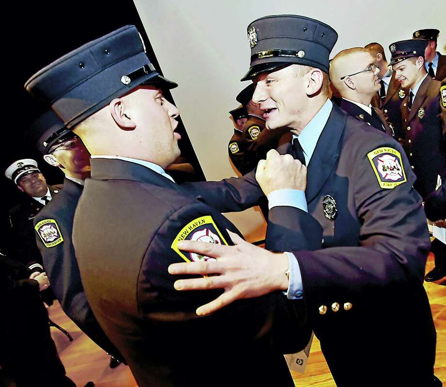 New Firefighter Mike Bianchi, right, a member of the 59th Fire Department recruiting class of the New Haven Fire Academy, hears on graduation night from James Kiley, a friend who joined the fire department in November, that the two both have been assigned to the Dixwell Fire Station. Photo: Catherine Avalone — New Haven Register       / New Haven RegisterThe Middletown Press