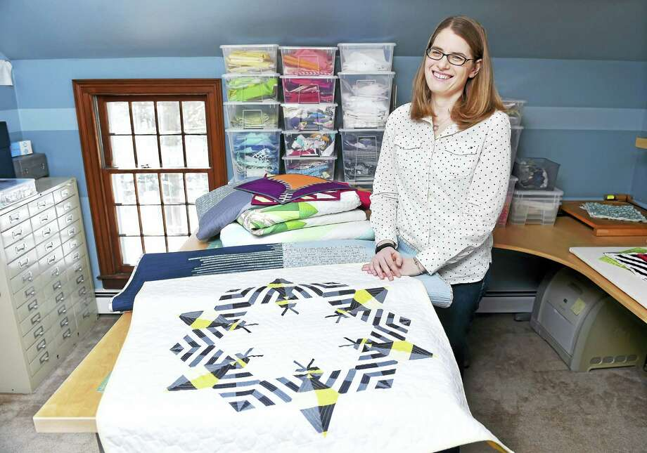 (Arnold Gold-New Haven Register)  Sheri Cifaldi-Morrill in the quilting studio of her home in Woodbridge recently.  In the foreground is the quilt, Bzzzzzz, which is one of five accepted to QuiltCon in Pasadena, California, to be held Feb. 18-21. Photo: Journal Register Co.