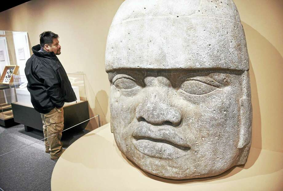 """Evarardo Zarate of Hamden looks at a fiberglass cast of an Olmec head dating back to 1200-900 BCE from Veracruz, Mexico, at the """"Treasure of the Peabody"""" exhibit celebrating the 150th anniversary of the Yale Peabody Museum of Natural History on April 02, 2016. Photo: Arnold Gold —New Haven Register"""