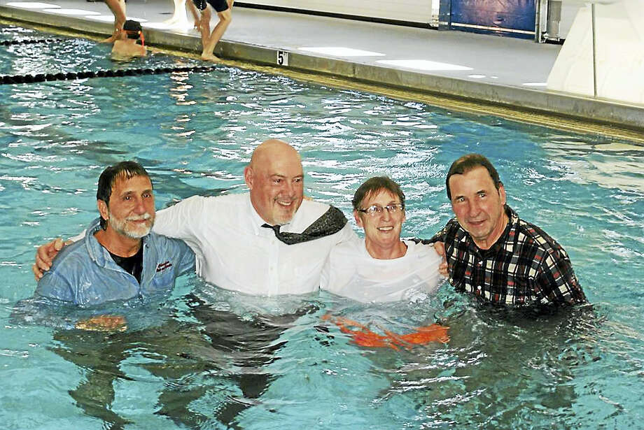 Tim Slocum photo  From left, in a celebratory dip in the pool, are Town Manager Michael Milone, Parks and Recreation Director Bob Ceccolini, Aquatics Director Sheila Adams and Public Building Commission Mark Nash. Photo: Journal Register Co.