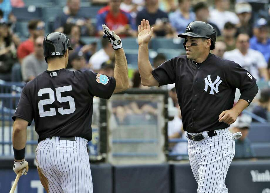 The Yankees' Jacoby Ellsbury, right, high fives Mark Teixeira after scoring in the fifth inning Saturday. Photo: Chris O'Meara — The Associated Press   / AP