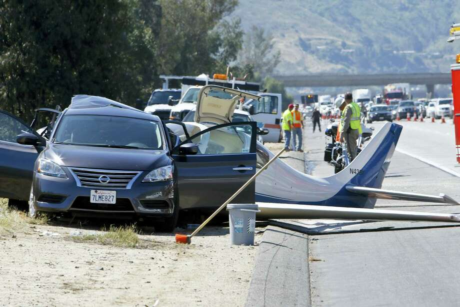 Emergency personnel investigate the scene of plane crash, Saturday, April 2, 2016 in Fallbrook, Calif. A small plane crashed on a Southern California freeway Saturday and struck a car, killing one person and injuring five others, authorities said. Photo: Don Boomer — The San Diego Union-Tribune Via AP   / The San Diego Union-Tribune