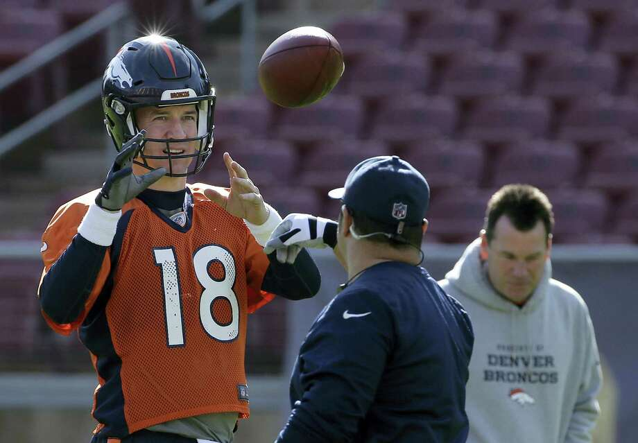 Broncos quarterback Peyton Manning (18) catches a ball during practice on Thursday. Photo: Jeff Chiu — The Associated Press   / AP