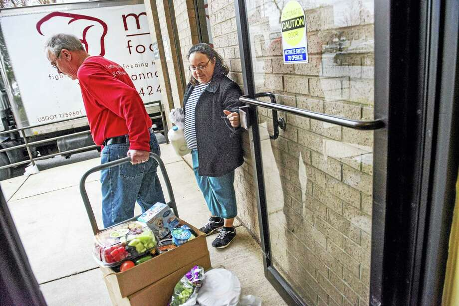Rosalba Diaz holds the door for volunteer Dean Swanson on Thursday at Gaithersburg, Maryland's Manna Food Center. As of Friday, food-stamp recipients in Maryland face a work mandate. Photo: Photo By Amanda Voisard For The Washington Post / For The Washington Post