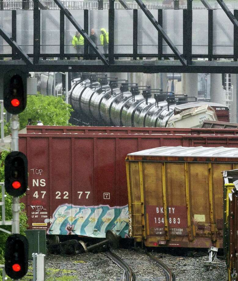 Officials look down from a Metro pedestrian bridge at several overturned train cars after a CSX freight train derailed in Washington on May 1, 2016. Photo: AP Photo/Cliff Owen   / Cliff Owen