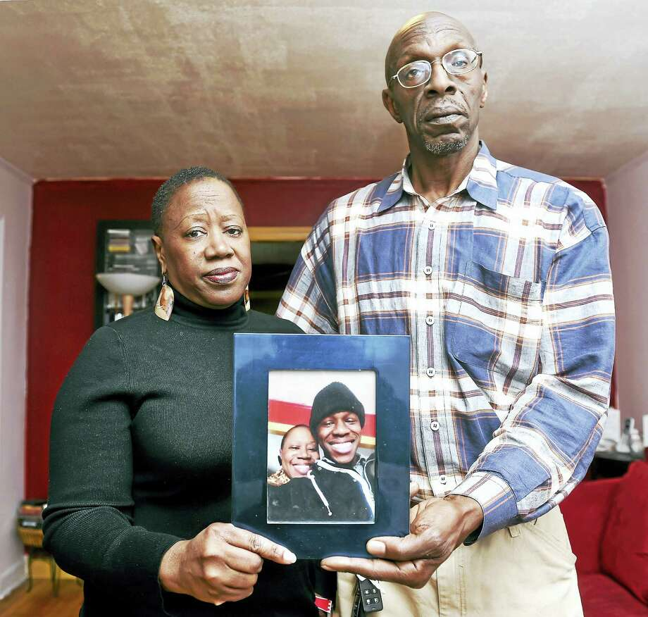 Odell Montgomery Cooper (left) and Michael C. Cooper, hold a photograph of their deceased son, Jonathan, at their home in New Haven. Photo: Arnold Gold-New Haven Register