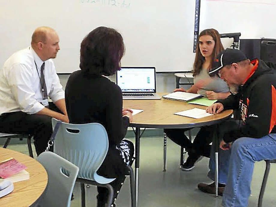 High School in the Community freshman Juliana Sabin, second from right, leads a conference between her parents, Lia and Kevin, and her academic adviser Ryan Hanover, left, in lieu of a traditional parent-teacher conference. Photo: Brian Zahn - New Haven Register