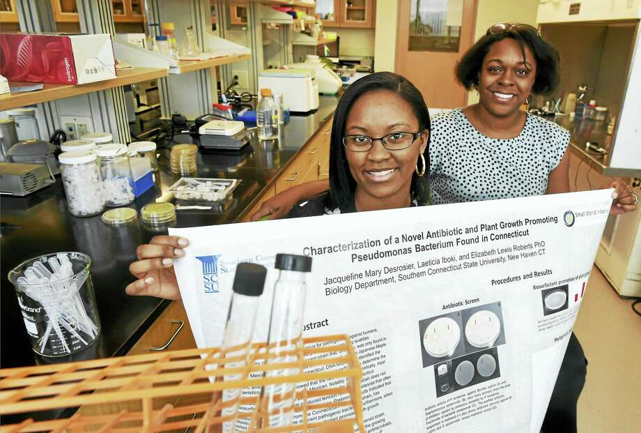 Laeticia Iboki, an SCSU biology major, left, displays a poster about her work with Professor Elizabeth Lewis Roberts of Southern Connecticut State University. Photo: Peter Hvizdak - New Haven Register   / ©2016 Peter Hvizdak