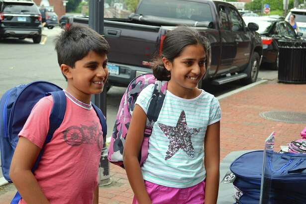 Sebastian Saridakis, 9, left, and his sister Alexa, 10, of New Canaan, were all smiles at Verizon Wireless Zone's backpack giveaway event, Sunday, July 23, 2017, on Elm Street in New Canaan, Conn.