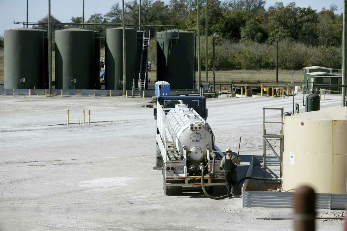 In this Wednesday, Nov. 19, 2014 photo, a fracking wastewater storage facility sits just outside the city limits of Reno, Texas.