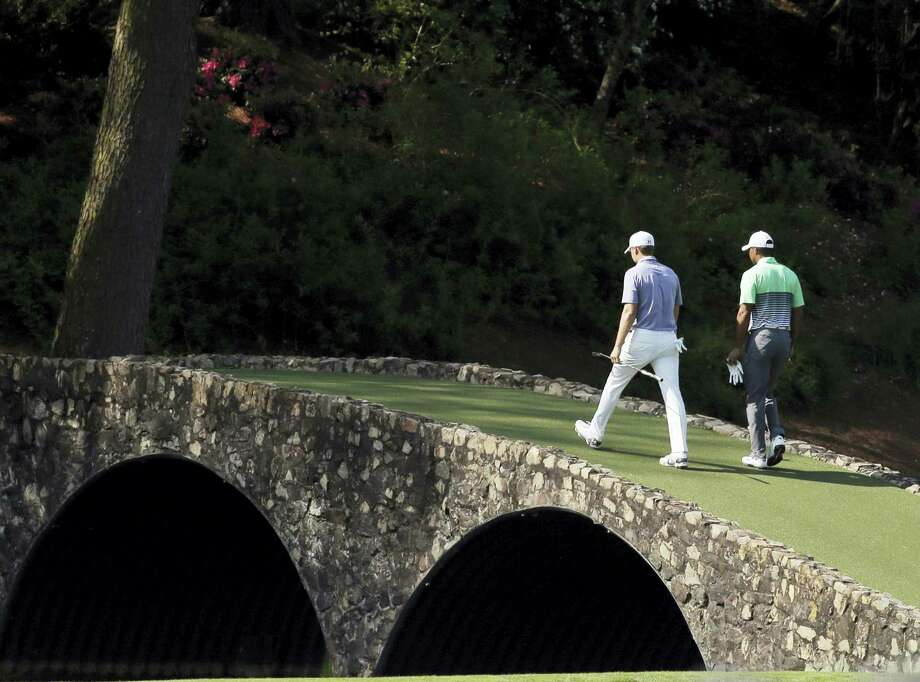 Tiger Woods, right, walks across the Ben Hogan Bridge with Jordan Spieth during a practice round for last year's Masters. Woods will not play in this year's Masters because of a back injury. Photo: The Associated Press File Photo   / AP