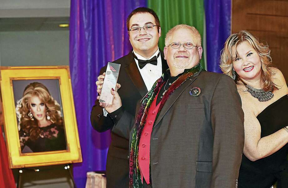 Joshua O'Connell, co-president of the New Haven Pride Center, at left, presents the Dorothy Award to Kenn Hopkins, the executive director and founder of the New England Ballet Company and his partner Sassie Saltimboca, pictured at left in the photograph, Saturday, March 5, 2016, at Fantasia in North Haven. At right is Christine O'Leary who introduced Ken and Sassie, who lost her battle to cancer on Aug. 17, 2015, a day after the couple made plans to marry. Photo: Catherine Avalone — New Haven Register    / New Haven RegisterThe Middletown Press