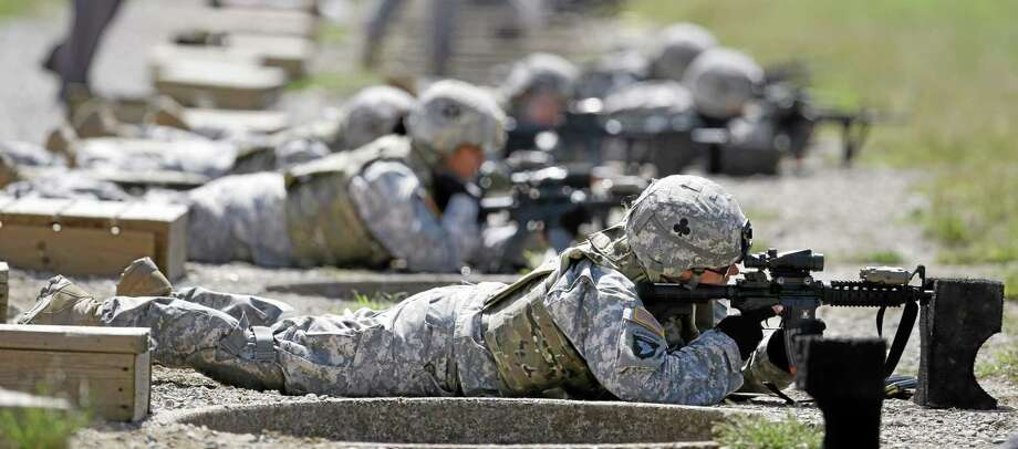 FILE - In this Sept. 18, 2012 file photo, female soldiers from 1st Brigade Combat Team, 101st Airborne Division train on a firing range while testing new body armor in Fort Campbell, Ky., in preparation for their deployment to Afghanistan. The Pentagon is lifting its ban on women serving in combat, opening hundreds of thousands of front-line positions and potentially elite commando jobs after generations of limits on their service, defense officials said Wednesday, Jan. 23, 2013. Photo: AP Photo/Mark Humphrey, File / AP