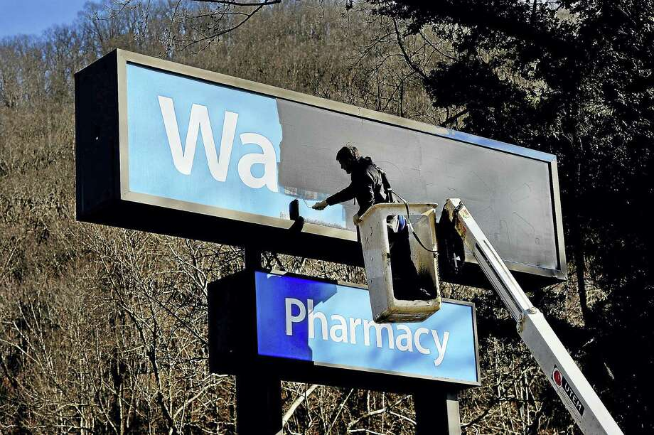 Five days after the store closing in Kimball, W.V., Guy Looney was hired to paint over the Walmart sign with black paint. He was also part of a crew that removed the large letters from the store building. The store closed its doors on Jan. 28, the latest blow to a struggling coal town. Photo: Washington Post Photo By Michael S. Williamson / The Washington Post