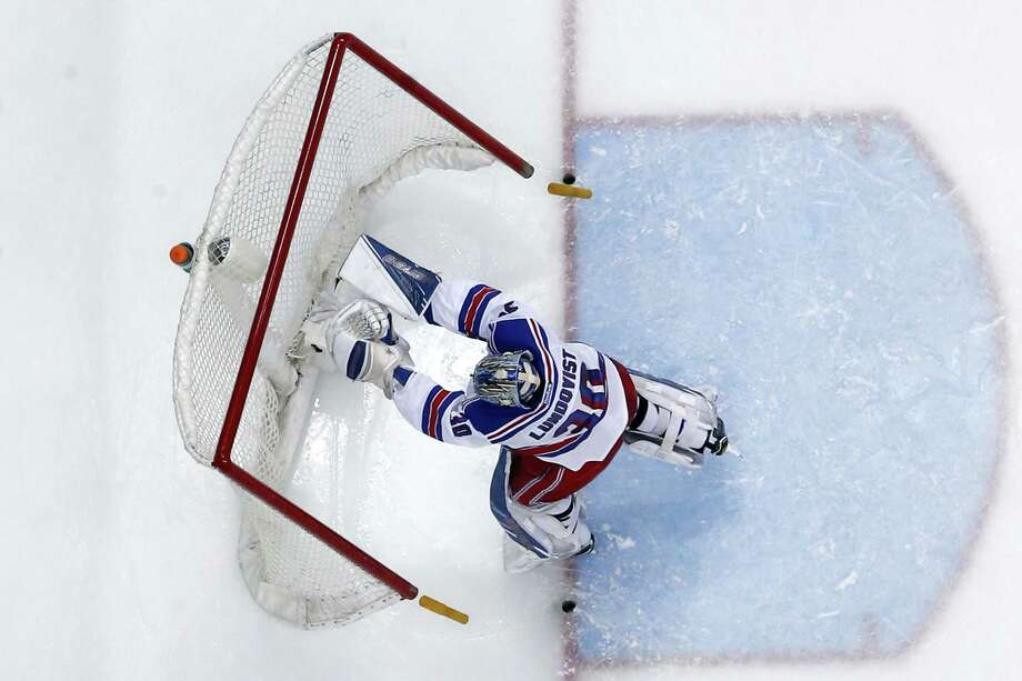 Rangers goalie Henrik Lundqvist (30) pushes over the goal cage to force a stoppage of play after being shaken up in a collision with teammate Ryan McDonagh during the second period against the Penguins on Thursday. Photo: Gene J. Puskar — The Associated Press   / AP