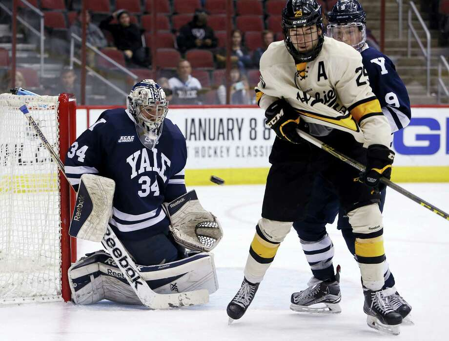Yale goalie Alex Lyon (34) makes the save in front of Michigan Tech forward Evan Anderson during the third period of an NCAA college hockey game at the Desert Hockey Classic tournament, Sunday, Jan. 10, 2016, in Glendale, Ariz. (AP Photo/Rick Scuteri) Photo: AP / FR157181 AP