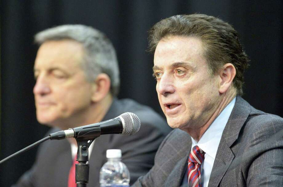 Louisville head basketball coach Rick Pitino, right, addresses the media following the University's announcement of a one-year postseason ban for its men's basketball team. Photo: Timothy D. Easley — The Associated Press   / FR43398 AP