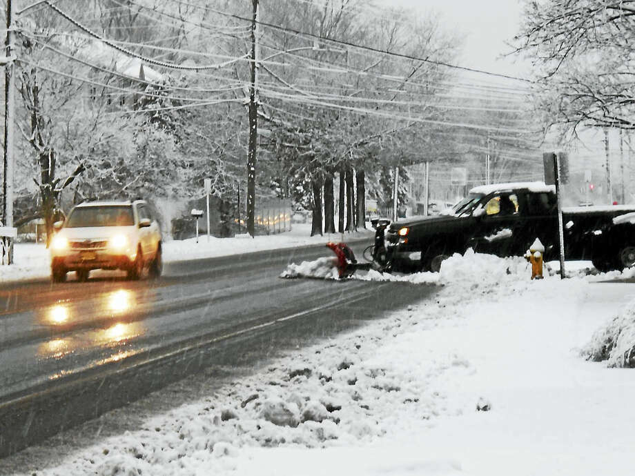 A plow pushes snow out onto Middletown Avenue in New Haven as commuters battle through heavy wet flakes to get to work. Photo: (Wes Duplantier -- The New Haven Register)