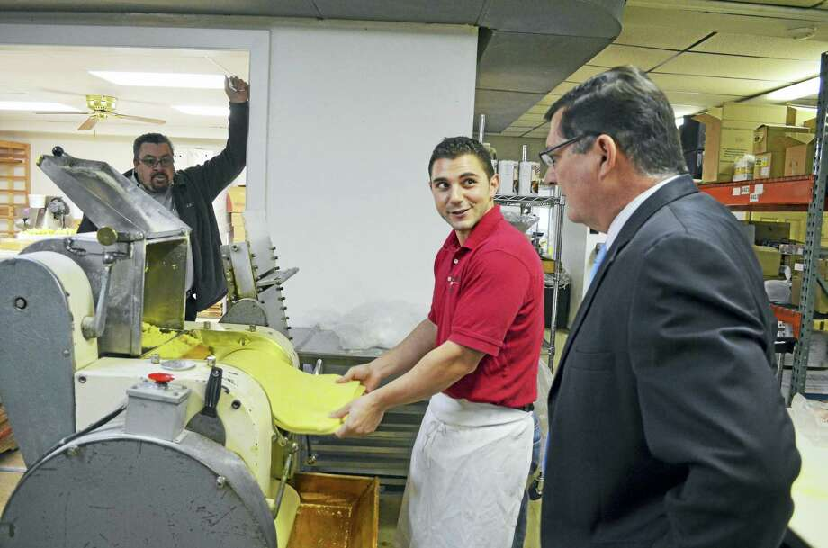 "Making Italian food taste better: Angelo Durante, owner of Durante's Pasta Inc. at 78 Fenwick St. in West Haven, uses a century-old machine from Genoa, Italy, to sheet pasta dough Dec. 22 as Mayor Edward M. O'Brien, front, and his constituent complaints officer, Francis Withington, look on. O'Brien, who was also accompanied by City Council Chairman James P. O'Brien, D-6, and Planning and Development Commissioner Joseph A. Riccio Jr., paid a midday visit to the corner of Fenwick and Yates streets in the city's Allingtown section to see the family-owned pasta business in full swing. The business, founded in 1985 by Durante's parents, Amadeo and Carmelina Durante, specializes in all varieties of home-style, fresh pasta. Angelo Durante, who lives in Ansonia, took over operation seven years ago from his parents, who hail from Derby. Durante's gourmet pasta products are made on the premises and sold in the front market, and also are available at select Italian restaurants in southern Connecticut. For information, visit <a href=""http://www.durantepasta.com"">www.durantepasta.com</a>. Photo: CONTRIBUTED PHOTO — MICHAEL P. WALSH"