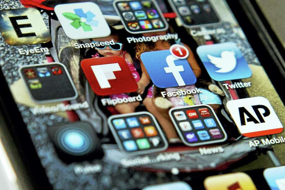 FILE - In this May 21, 2013 file photo, a view of an iPhone in Washington showing the Twitter apps among. Twitter is now using spam-fighting technology to seek out accounts that might be promoting terrorist activity and is proactively looking at other accounts related to those flagged for possible removal, the company announced Friday. Photo: AP Photo/Evan Vucci, File / AP