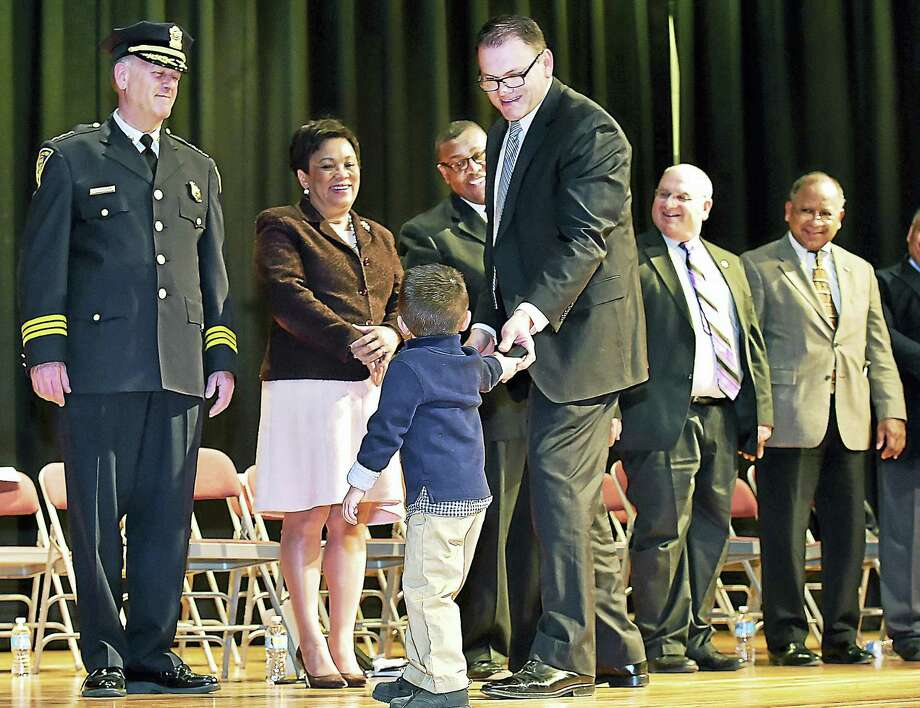 Three-year-old Nico Tolnay anxiously presents the detective shield he received from Chief of Police Dean M. Esserman, to his father, Arpad Tolnay, a 17-year-veteran of the force at the New Haven Police Department Detective Promotional Ceremony, Friday, March 4, 2016, at Hill Regional Career High School in New Haven. Nico and his maternal grandfather NHPD Detective Mac Caporale were on stage to present Tolnay his shield. Photo: Catherine Avalone — New Haven Register
