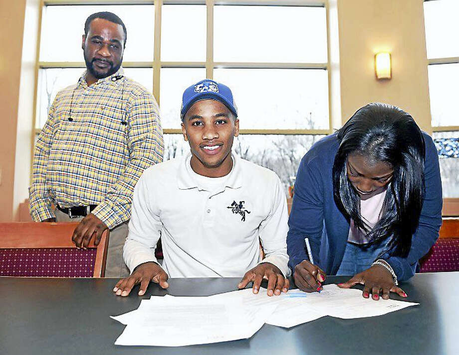 Ansonia's Tajik Bagley (center) is joined by his father, Shawn Bagley (left), and mother, Taishka Addison, Wednesday at Ansonia High School, during the signing of a letter of intent to attend Central Connecticut State University. Photo: Arnold Gold — New Haven Register