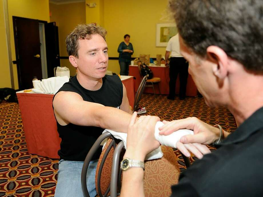 "Trainer Colin Albert, Bridgewater, tapes the hands of Ryan Clifford, Stamford, before his boxing match. By day, Clifford is a trader for Energy Trading Company. The amateur boxer is part of a charity event called the ""Real Fight Club Stamford,"" hosted by the Revolution Fitness Youth Foundation of Stamford at the Stamford Holiday Inn on Friday June 11, 2010. Proceeds will benefit Hope for Haiti, the Revolution Fitness Youth Foundation and the local chapter of USA Boxing. A three-course dinner is also part of the $100-per-ticket event. Photo: Shelley Cryan / Shelley Cryan"