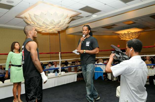 """Ahmad Mickens, center, introduces the evening's events in the ring. He's the founder of Revolution Fitness, and has organized amateur boxers as part of a charity event called the """"Real Fight Club Stamford,"""" hosted by the Revolution Fitness Youth Foundation of Stamford at the Stamford Holiday Inn on Friday June 11, 2010. Proceeds will benefit Hope for Haiti, the Revolution Fitness Youth Foundation and the local chapter of USA Boxing. A three-course dinner is also part of the $100-per-ticket event. Photo: Shelley Cryan / Shelley Cryan"""