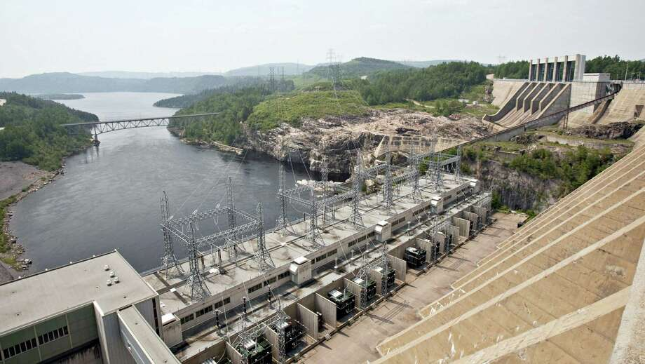 In this June 22, 2010 file photo, the Jean-Lesage hydro electric dam generates power along the Manicouagan River north of Baie-Comeau, Quebec. Long-term plans to bring clean Canadian electricity to the power hungry markets of southern New England are getting a big boost from the decision by Vermont utility regulators, who approved a plan to build a 1,000 megawatt transmission line that would run beneath Lake Champlain and then be buried in public rights of way to the town of Ludlow, Vt. TDI New England is still awaiting its final federal permits and contracts to deliver power, but hope to begin construction next year with power beginning to flow in 2019. Photo: Jacques Boissinot/The Canadian Press Via AP, File / CP