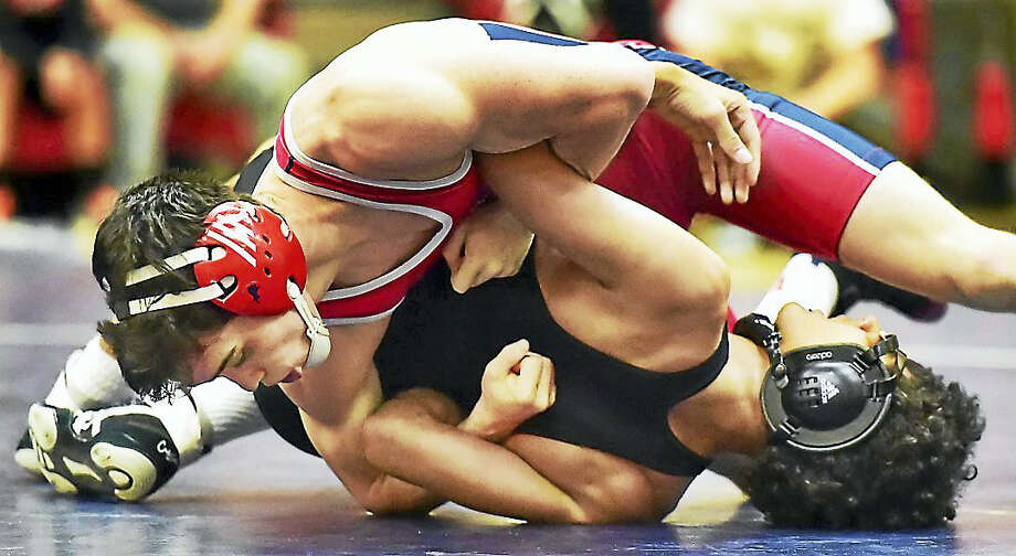 Foran senior Jubilee Witte battles Law sophomore Jordan Beck, chalking up a win in the 132 lb. weight class Thursday at Foran High School gymnasium in Milford. The Foran Lions defeated the Lawmen of Jonathan Law High School, 72-7. Photo: Catherine Avalone/New Haven Register   / Catherine Avalone/New Haven Register
