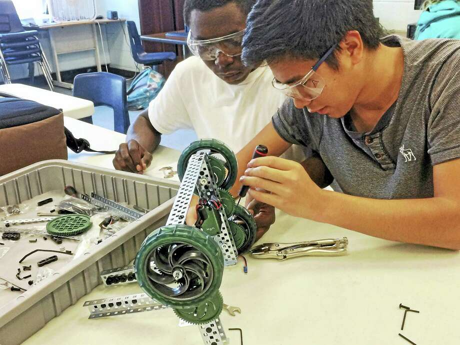 West Haven High School STEM students Oreo Olowe, a junior, left, and James Delgado, a sophomore, work on a robotics project in advance of University of New Haven's Feb. 13 competition. Photo: Contributed Photo