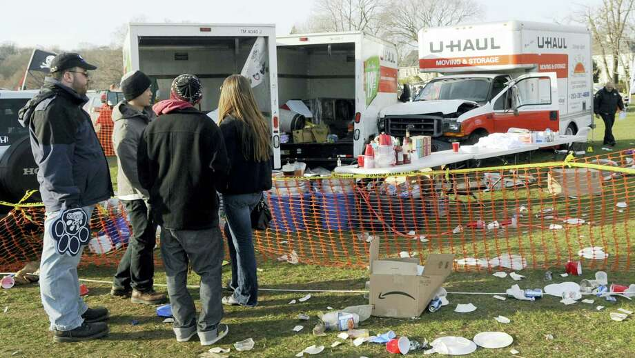 In this Nov. 19, 2011 file photo, people look at the scene of a fatal accident in a parking area outside an NCAA college football game between Harvard and Yale in New Haven. Photo: Associated Press   / FR 170410 AP