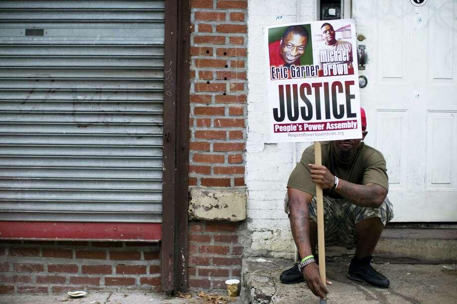 FILE- In this Aug. 23, 2014 file photo, a demonstrator holds a sign bearing the likeness of Eric Garner and Michael Brown before a march to protest the death of Garner in the Staten Island borough of New York. On Friday, Jan. 8, 2016, New York Police Department Sgt. Kizzy Adonis has been stripped of her gun and badge and charged internally in Garner's death. It's the first official accusation of wrongdoing in the case that helped spark a national movement on the role of race in policing. Photo: AP Photo/John Minchillo, File / FR170537 AP