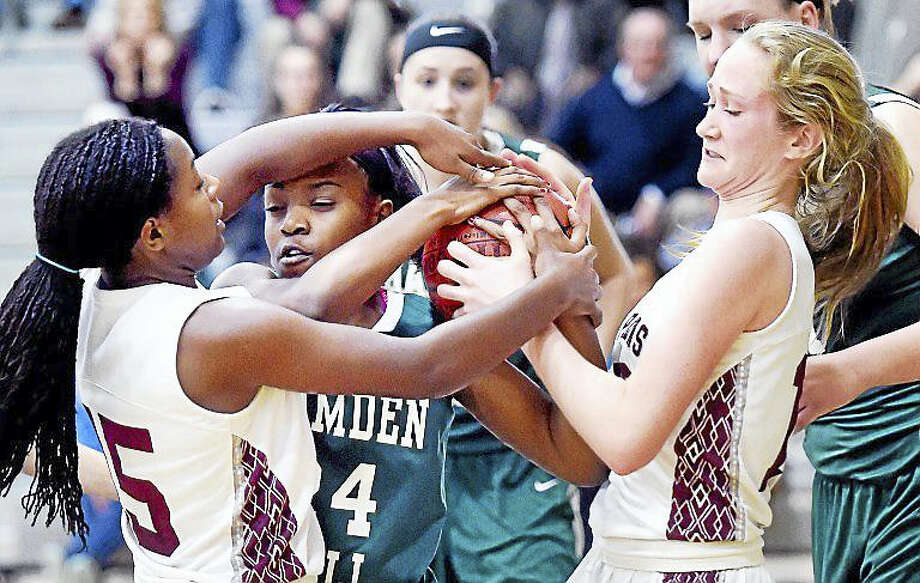 Alex McCraven (left) and Galen Smith (right) of Hopkins fight for the ball Tuesday with Courtney Joshua of Hamden Hall. Photo: Arnold Gold — New Haven Register