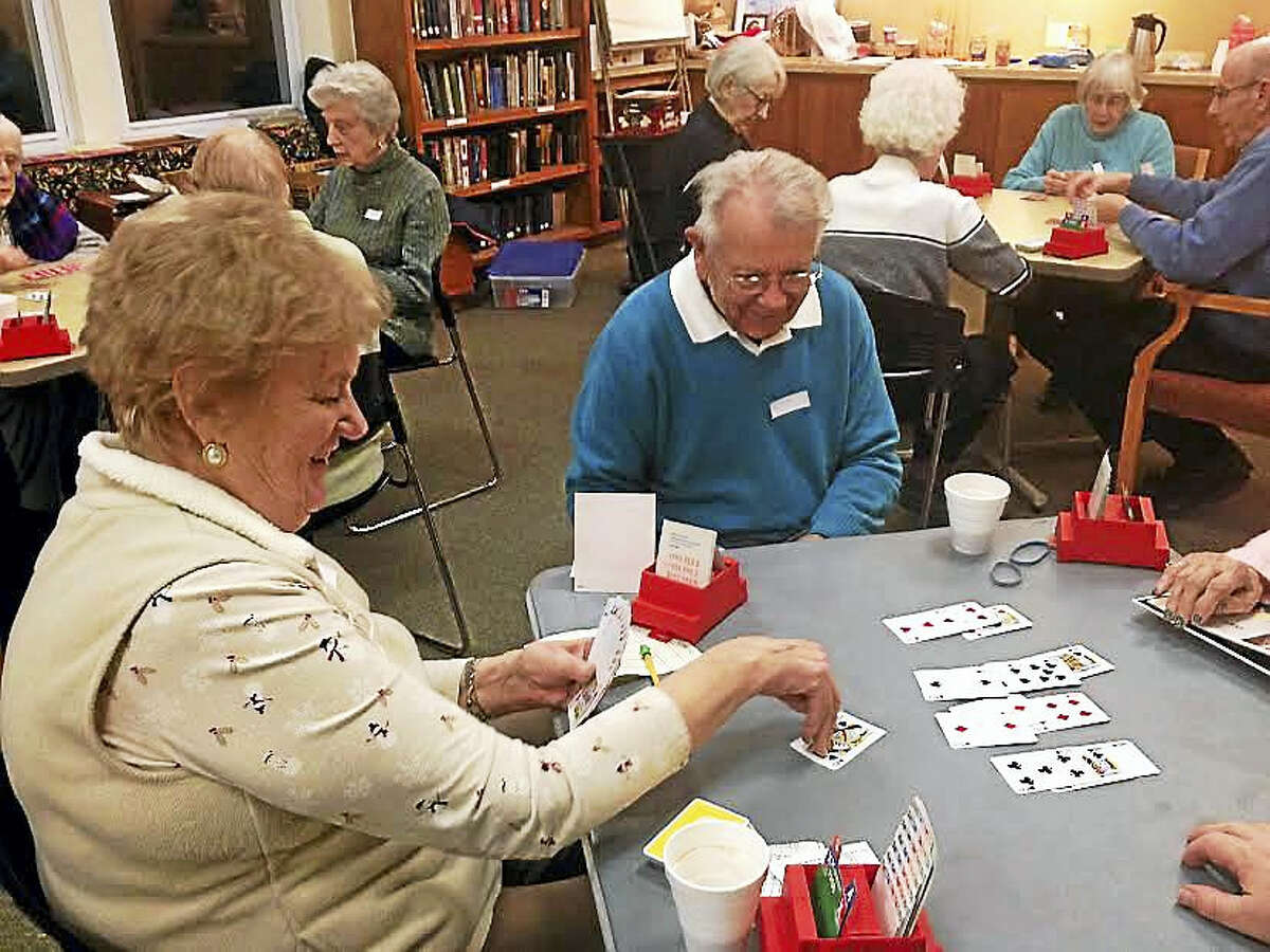 Singles Intermediate Bridge Group President Maggie Clancy, left, and one of the group's founders, Carl Yohans, play a game of bridge with others from the group celebrating its 35th anniversary.
