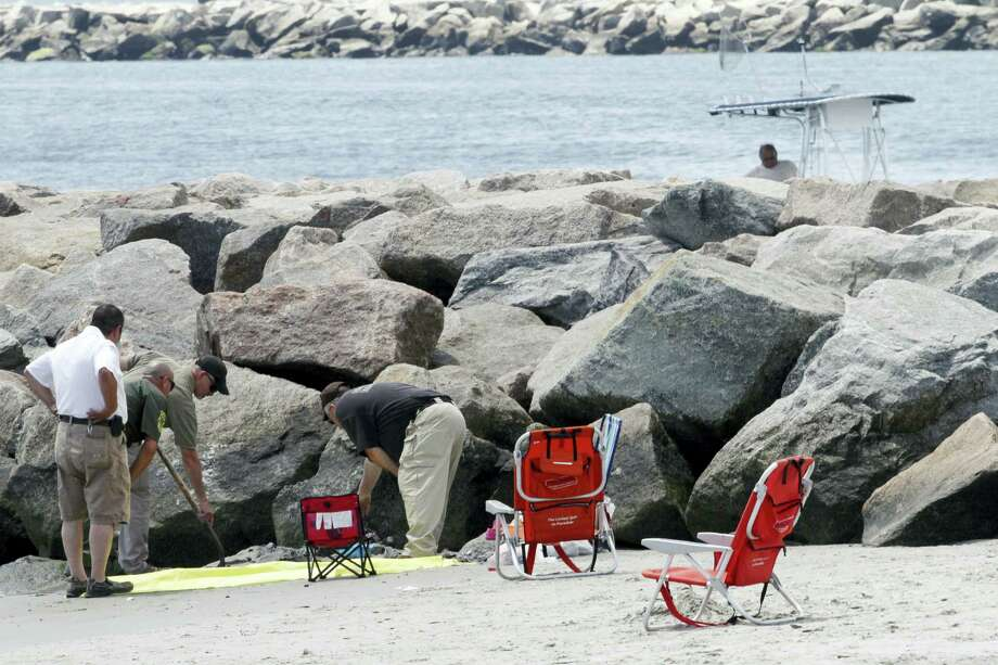 In this July 11, 2015, photo, authorities investigate a blast that threw a beachgoer into a nearby jetty at Salty Brine beach in Narragansett, R.I. Photo: Steve Szydlowski — Providence Journal Via AP   / Providence Journal