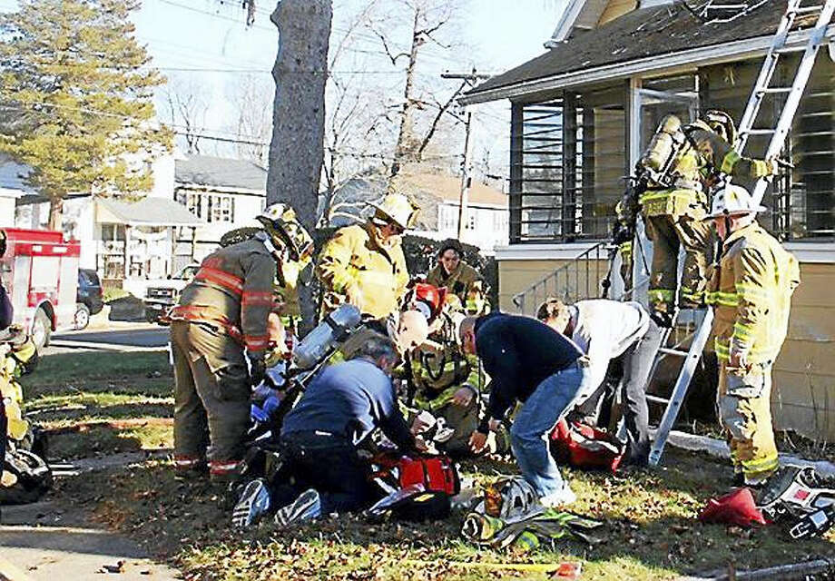 East Haven firefighters rescue a man who was found unconcious in his burning home on Jan. 6. Photo: CONTRIBUTED PHOTO — Joseph Ciscone