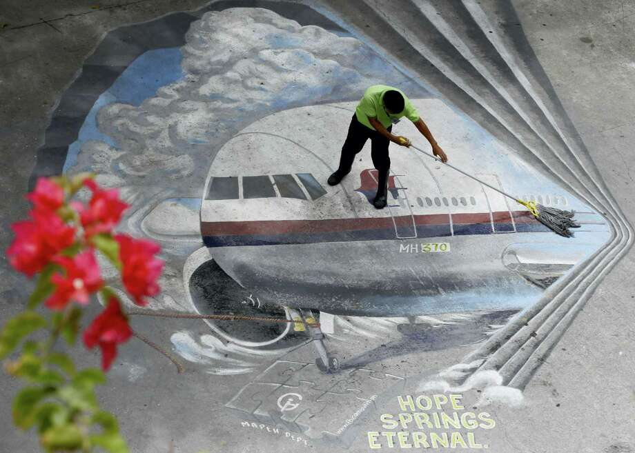 """FILE - In this April 8, 2014, file photo a school utility worker mops a mural depicting the missing Malaysia Airlines Flight 370 at the Benigno """"Ninoy"""" Aquino High School campus at Makati city east of Manila, Philippines. A U.S. official says debris washed up over the weekend in Mozambique has been tentatively identified by experts close to the investigation as a part from the tail of the same type of aircraft as the missing Malaysia Airlines Flight 370. Photo: AP Photo — Bullit Marquez, File / AP"""