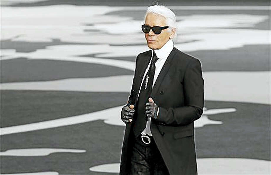In this March, 5, 2013, file photo, German fashion designer Karl Lagerfeld acknowledges applause at the end of his Fall/Winter 2013-2014 ready to wear collection for Chanel presented in Paris. French authorities are investigating designer Karl Lagerfeld's taxes and a French magazine says he used offshore tax havens to avoid paying millions of euros to the French government. The case is the latest involving allegations of high-end tax evasion in France, where the Finance Ministry has cracked down on fraud in recent years to ease budget strain. Photo: AP Photo/Christophe Ena, File   / AP