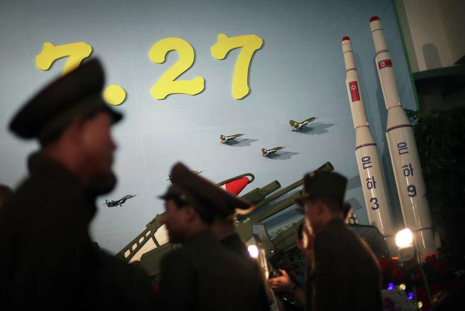In this July 26, 2013, photo, North Korean soldiers are silhouetted against model versions of the Unha 3 space launch vehicle which successfully delivered North Koreaís first satellite into Earth orbit, and the Unha 9, right, which would carry a lunar orbiter, on display at an annual flower show held in honor of national founder Kim Il Sung and his son Kim Jong Il, in Pyongyang, North Korea. Less than a month after its purported H-bomb test, the exact nature of which still has foreign analysts guessing, attention is now focused on whether North Korea is readying a rocket launch. There are indications including the construction of a new and taller gantry, visible in commercial satellite imagery that it could be a bigger and better version of the Unha 3 space launch vehicle that lifted off from the Sohae facility in 2012, on the west coast of North Korea. Photo: AP Photo/Wong Maye-E    / AP