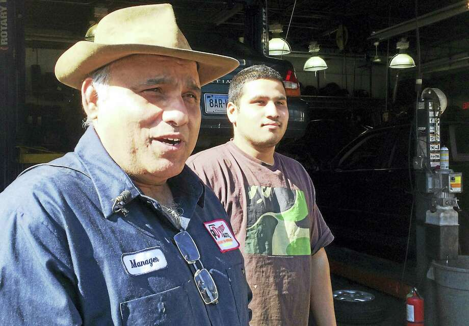 Sajjad Chaudhary and his son, Ali, speak to reporters Tuesday outside the family business, Dynamic Auto, 271 Whalley Ave., New Haven. Photo: Wes Duplantier — New Haven Register