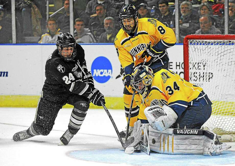 Providence's Noel Acciari's shot is stopped by Quinnipiac goaltender Michael Garteig (34) as Alex Barron (8) looks on during the first period during a game in the men's NCAA East Regional hockey tournament Friday, March 28, 2014, in Bridgeport, Conn. (AP Photo/Fred Beckham) Photo: AP / FR153656 AP