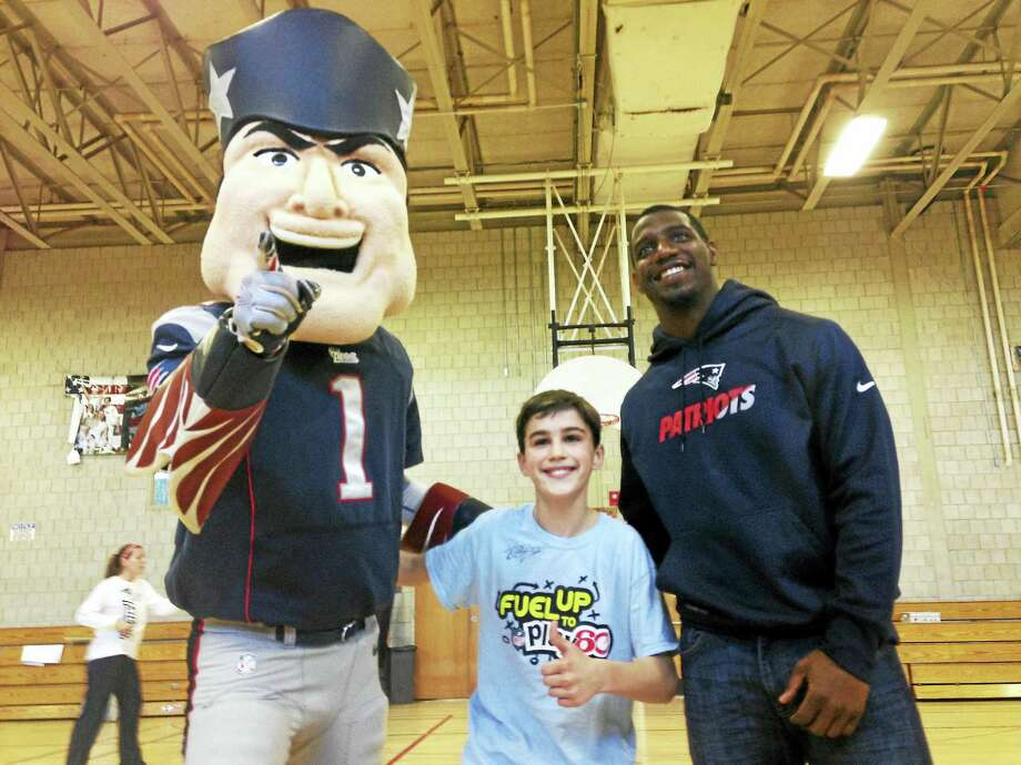 "Patriots mascot ""Pat Patriot,"" William Mollow and Patriots safety Duron Harmon pose for a photo in the Walsh Intermediate School gym Tuesday morning in Branford. Photo: Juliemar Ortiz — New Haven Register"