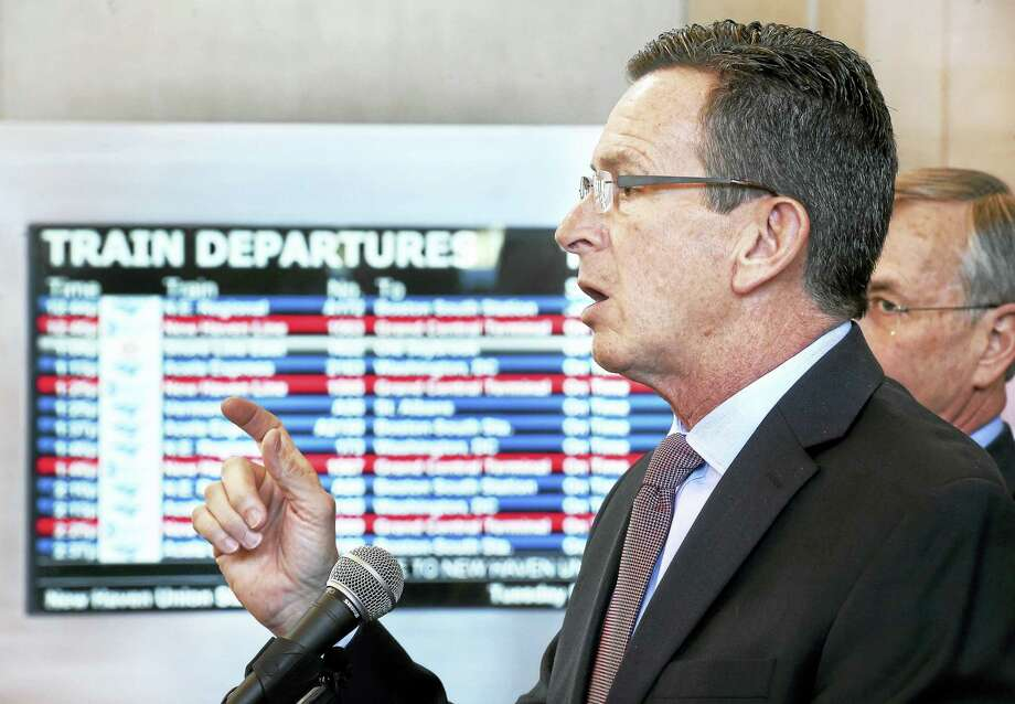 State Department of Transportation Commissioner James Redeker, right, listens to Gov. Dannel P. Malloy talk about the record ridership for the Metro-North Railroad during a press conference at Union Station in New Haven Tuesday. Photo: ARNOLD GOLD — NEW HAVEN REGISTER