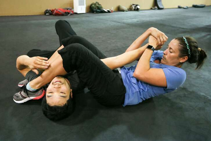 Meagan Harvey (right) pins an attacker, Nicholas West-Miles, after escaping from a choke hold during a KM 2/3 martial arts class at Krav Maga on July 14, 2017.