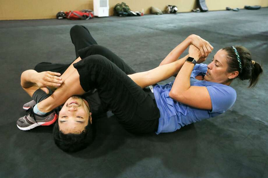 Meagan Harvey (right) pins an attacker, Nicholas West-Miles, after escaping from a choke hold during a KM 2/3 martial arts class at Krav Maga on July 14, 2017. Photo: Marvin Pfeiffer /San Antonio Express-News / Express-News 2017
