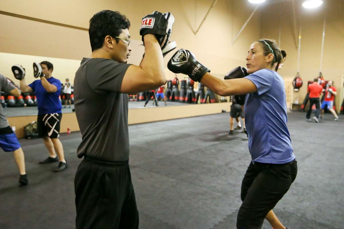 Meagan Harvey (right) does focus mitt work with Nicholas West-Miles during a KM 2/3 martial arts class at Krav Maga, 18450 Blanco Road, on July 14, 2017.